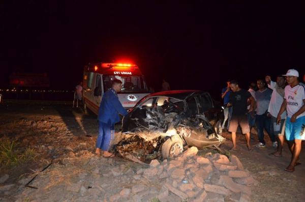 O carro teve a dianteira destruída na colisão. A porta abriu e o motorista caiu sobre o acostamento