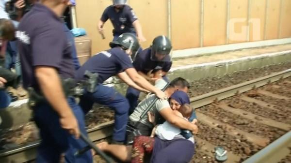 Policiais húngaros tentam separar uma família de migrantes. A face mais horrenda da estupidez humana.